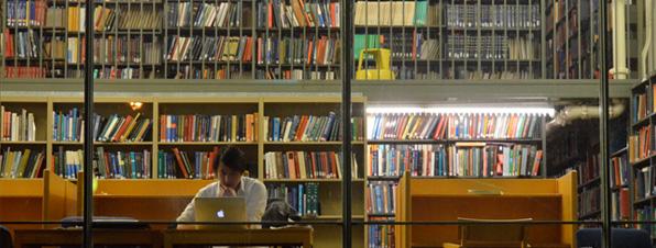 Usuario en biblioteca leyendo en un ordenador